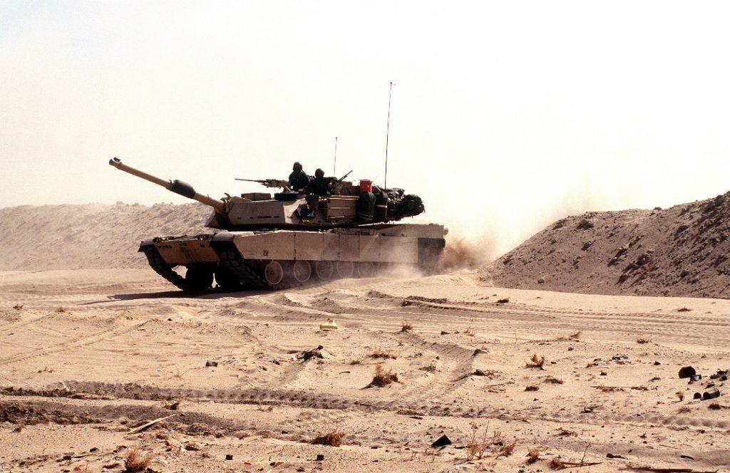 """Uno de los carros M1A1 del Grupo """"Cougar"""", tras franquear el terraplén en la frontera norte de Arabia Saudí el 23 de febrero de 1991Uno de los carros M1A1 del Grupo """"Cougar"""", tras franquear el terraplén en la frontera norte de Arabia Saudí el 23 de febrero de 1991"""