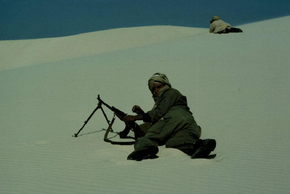 Durante el conflicto con el Polisario un observador apostado en la duna de arriba usa sus binoculares para observar al enemigo mientras otro soldado le proporciona seguridad mediante una ametralladora ligera RPK